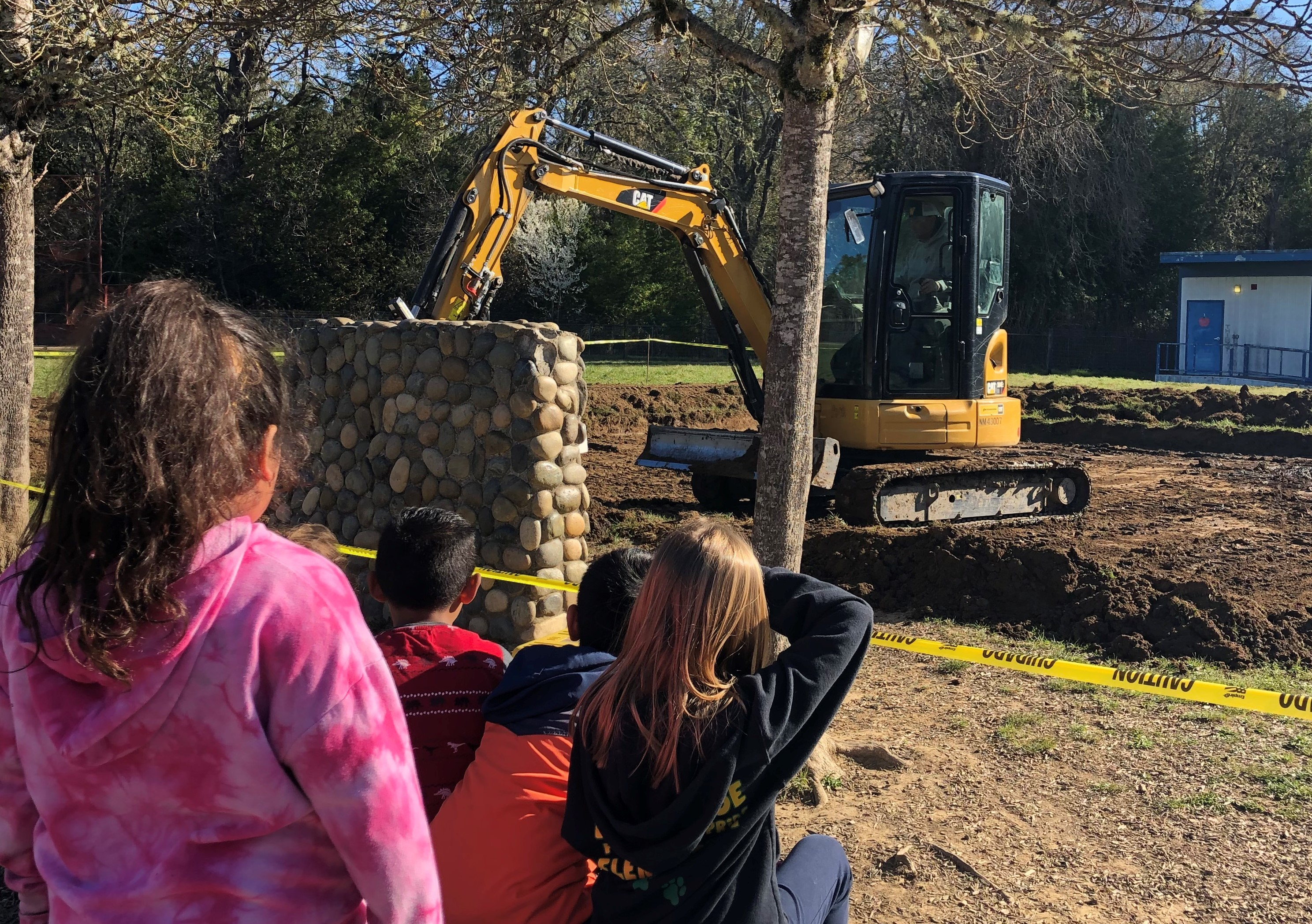 Brookside first graders watch Stan Cooley prepare the ground for our new playground equipment purchased with a grant written by our superintendent, Mr. Westerburg.